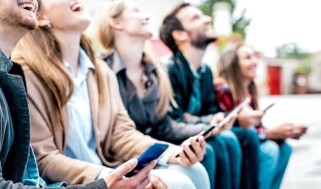 Freunde lachen, während sie smartphone an der universitätsuniversitätspause benutzen