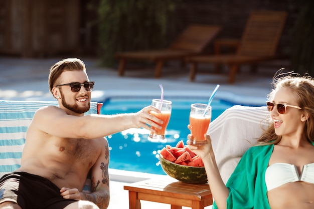Freunde lächeln, cocktails trinken, auf liegen in der nähe von schwimmbad liegen