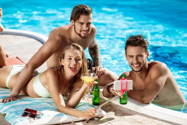 Freunde lächeln, machen selfie, trinken cocktails, entspannen in der nähe von schwimmbad