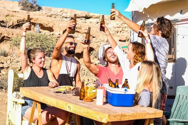 Freunde leute, die zusammen mit spaß auf einem alternativen ländlichen campingplatz im freien rösten