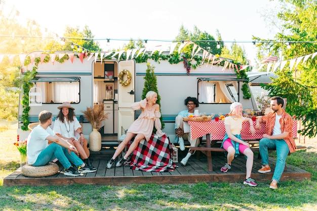 Freunde machen ein picknick mit einem camper auf einer grünen wiese