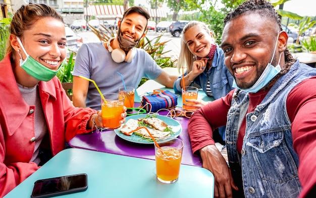 Freunde machen selfie in einem bar-restaurant mit gesichtsmaske