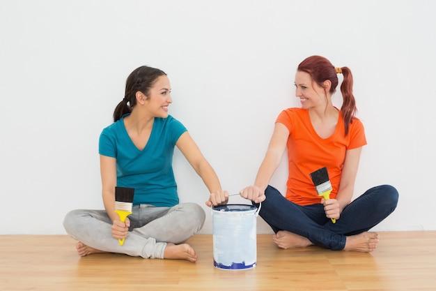Freunde mit bürsten und farbe können in einem neuen haus sitzen