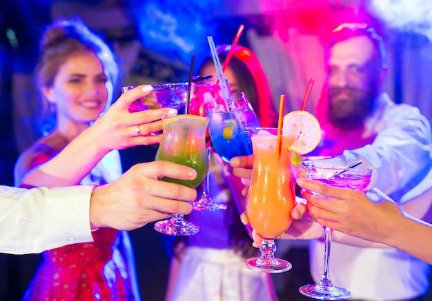 Freunde mit cocktails trinken auf einer party.