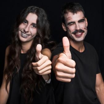 Freunde mit dem gespenstischen make-up, das daumen aufstellt