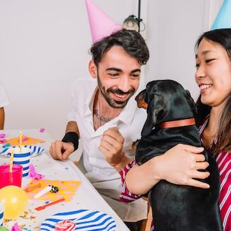 Freunde mit dem hund, der eine geburtstagsfeier feiert
