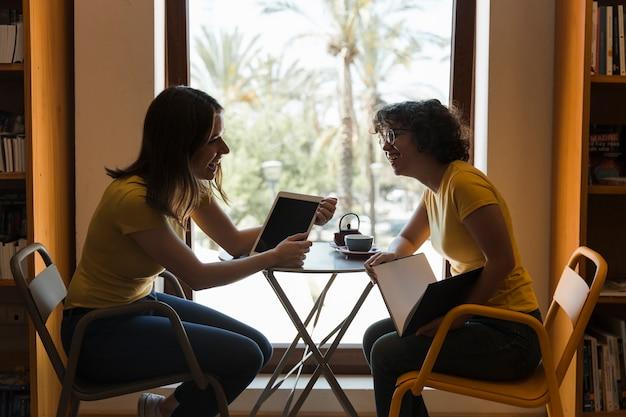 Freunde mit der tablette und buch, die in der bibliothek lachen