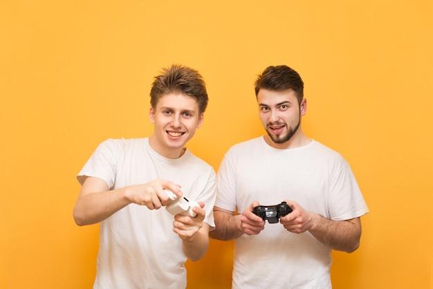 Freunde mit joysticks in den händen sind gelb