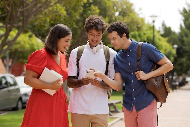 Freunde mit mittlerem schuss, die auf das telefon schauen