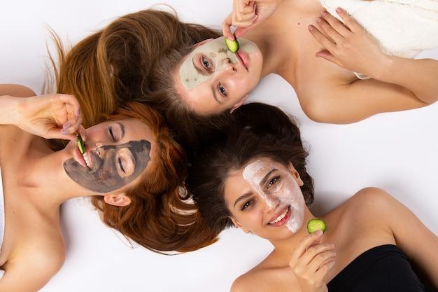 Freunde mit verschiedenen masken mit gurken und einem fröhlichen lächeln. spa-konzept. hochwertiges foto
