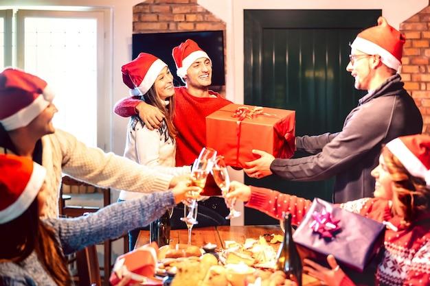 Freunde mit weihnachtsmütze geben sich gegenseitig weihnachtsgeschenk