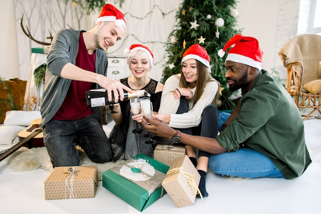 Freunde mit weihnachtsmützen feiern weihnachten mit champagner