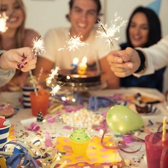Freunde mit wunderkerzen zur geburtstagsfeier