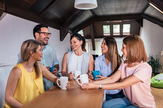 Freunde oder mitarbeiter, die spaß beim trinken des tees am zählertisch haben.