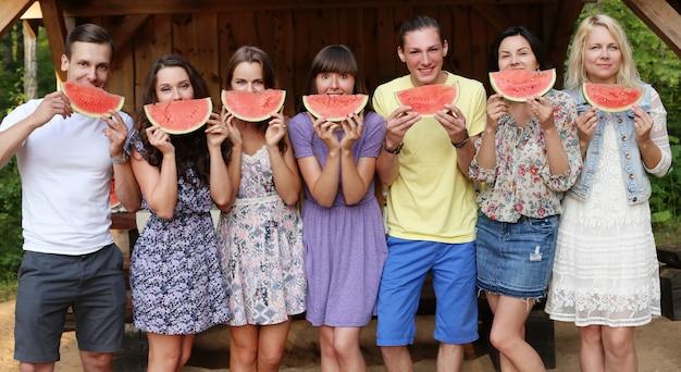 Freunde posieren mit wassermelonenscheiben