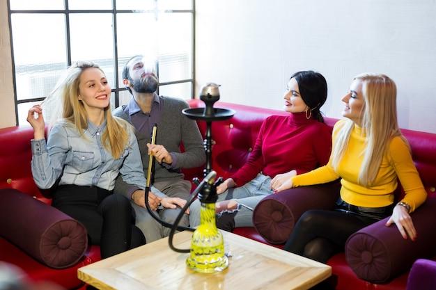 Freunde rauchen wasserpfeife und haben spaß, lachen.