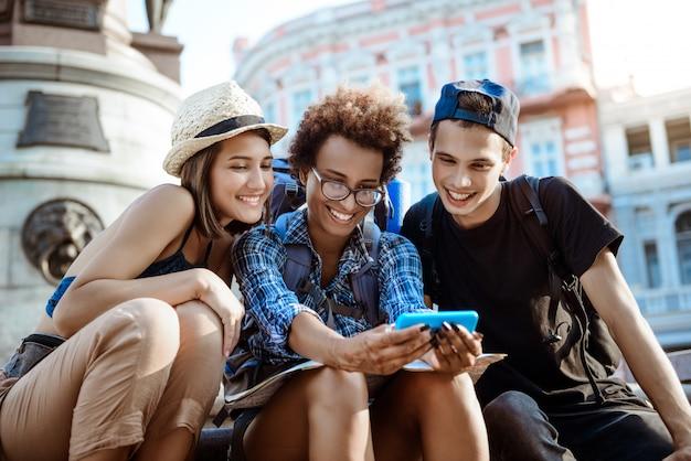 Freunde reisende mit rucksäcken lächelnd, selfie machen, in sichtweite sitzen.