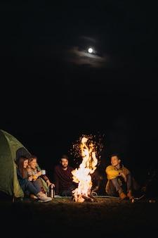 Freunde reisende sitzen vor dem lagerfeuer in der nacht