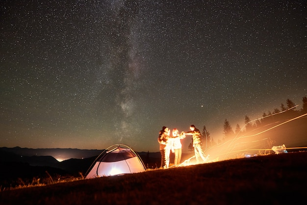 Freunde ruhen neben lager, lagerfeuer unter nächtlichem sternenhimmel Premium Fotos