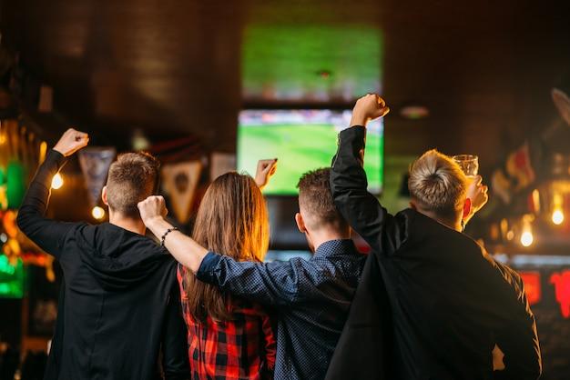Freunde schauen fußball im fernsehen in einer sportbar