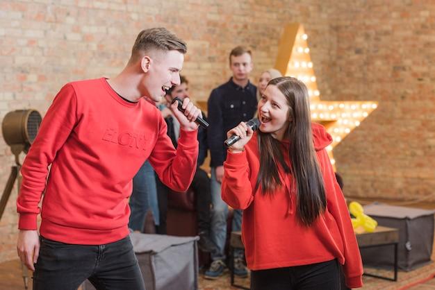 Freunde singen karaoke auf einer party