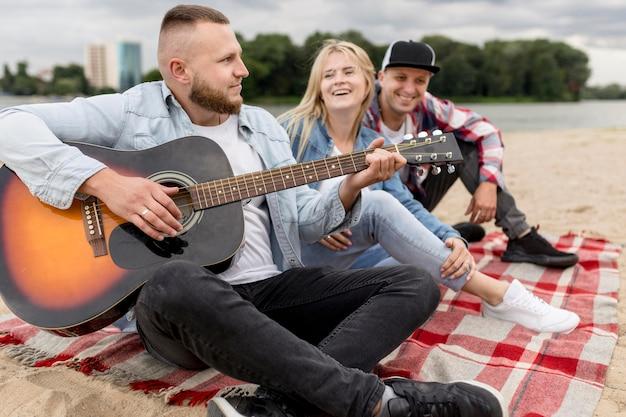 Freunde singen und spielen draußen gitarre