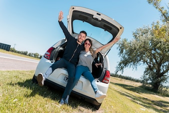 Freunde sitzen auf Autokofferraum machen Friedenszeichen