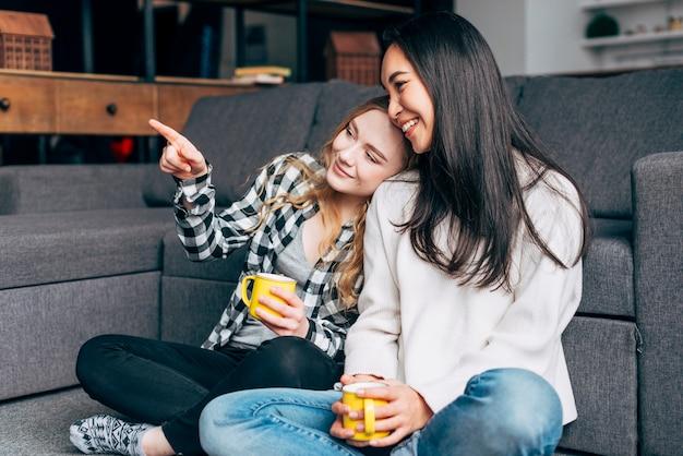 Freunde sitzen auf dem boden mit tee