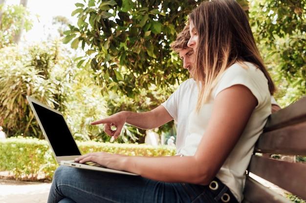 Freunde sitzen auf der bank mit einem notebook