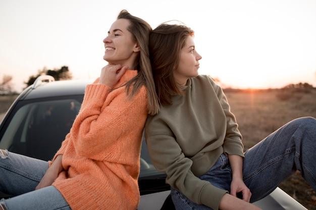Freunde sitzen auf einem auto