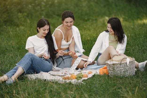 Freunde sitzen auf einem gras. mädchen auf einer decke. frau in einem weißen hemd.