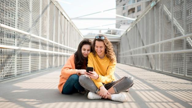 Freunde sitzen auf einer brücke und schauen auf ihr handy