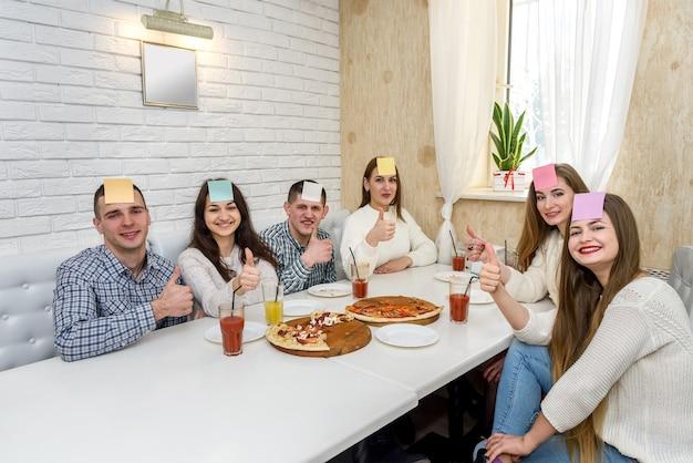Freunde sitzen im café und spielen 'rate wer' spiel