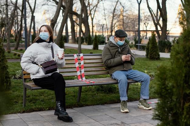 Freunde sitzen in der ferne und tragen maske