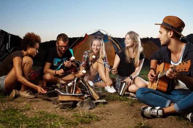 Freunde sitzen in der nähe von lagerfeuer, lächeln, gitarre spielen