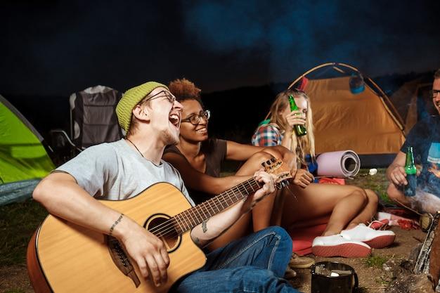 Freunde sitzen in der nähe von lagerfeuer, lächeln, sprechen, ruhen sich aus, spielen gitarre