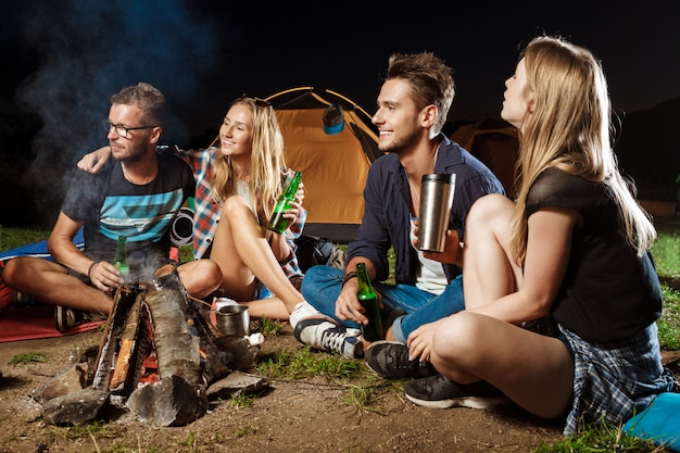 Freunde sitzen in der nähe von lagerfeuer, lächeln, sprechen, ruhen sich aus, trinken bären