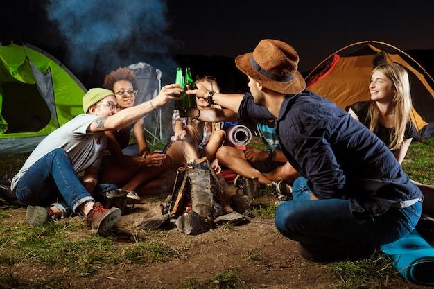 Freunde sitzen in der nähe von lagerfeuer, trinken bären, lächeln, sprechen, ruhen