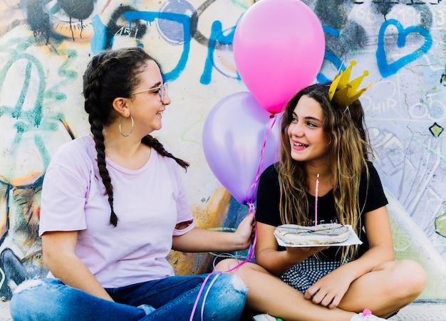 Freunde sitzen mit luftballons und geburtstagsgebäck