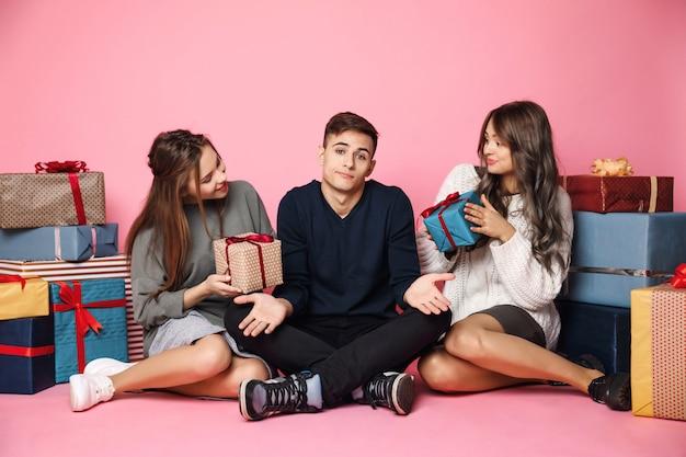 Freunde sitzen unter weihnachtsgeschenken auf rosa mann ohne box.