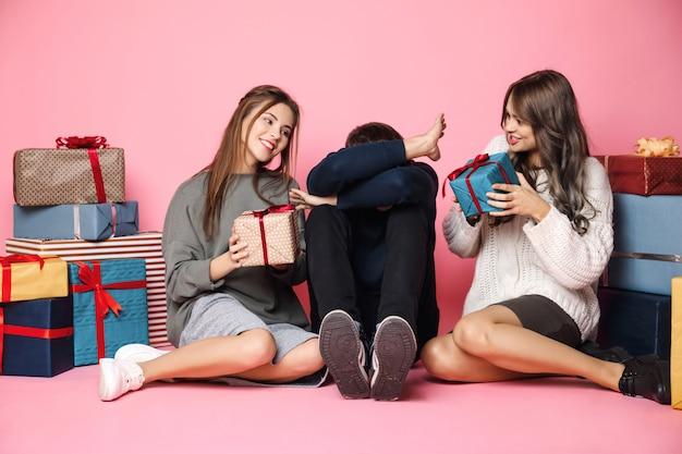 Freunde sitzen unter weihnachtsgeschenken auf rosa