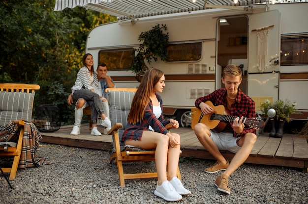 Freunde spielen auf der gitarre beim picknick auf dem campingplatz im wald. jugend mit sommerabenteuer auf wohnmobil, campingauto zwei paare freizeit, reisen mit anhänger