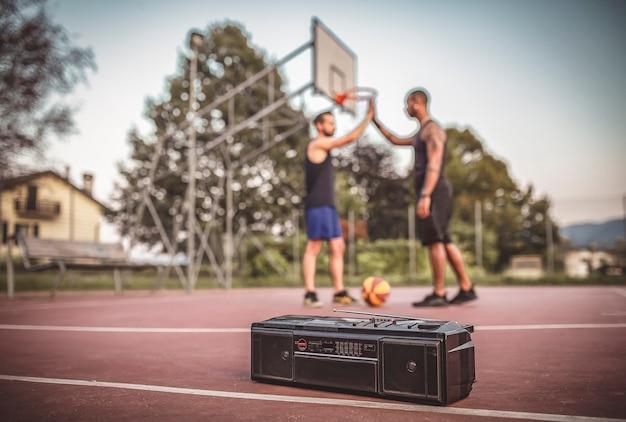Freunde spielen basketball auf einem platz im freien