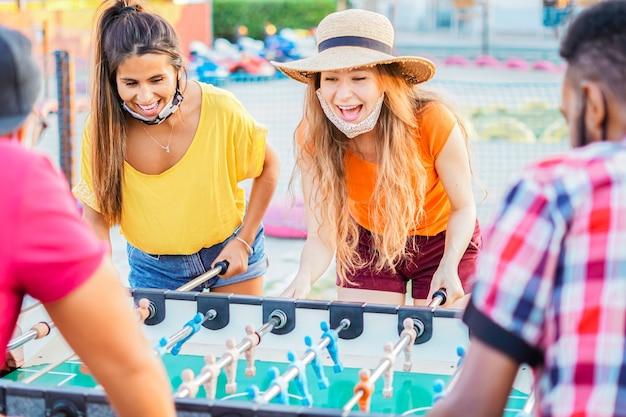 Freunde spielen gerne mit dem tischfußball - jugendliche mit gesichtsmaske im urlaub