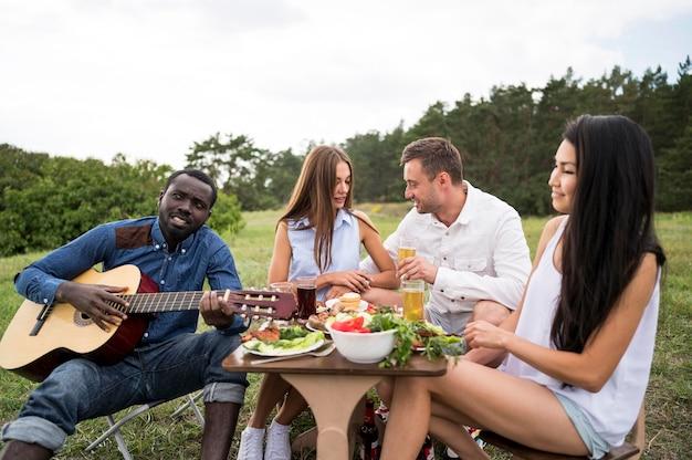 Freunde spielen gitarre und essen beim grillen