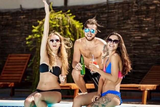 Freunde sprechen, lächeln, cocktails trinken, sich ausruhen, in der nähe des schwimmbades entspannen