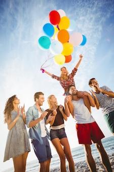 Freunde tanzen auf sand mit ballon