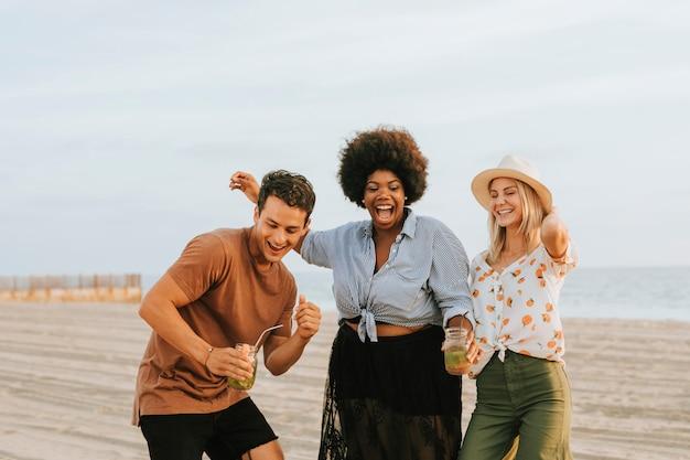 Freunde tanzen und haben spaß am strand