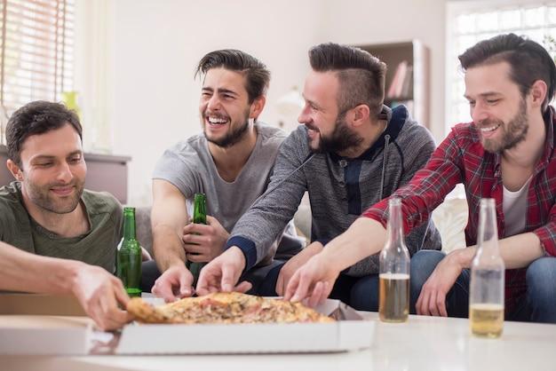 Freunde trinken bier und essen pizza