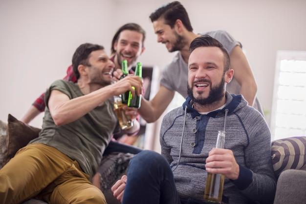 Freunde trinken bier und schauen fußballspiel